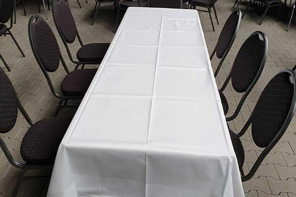 Eckiger, gedeckter Tisch mit schwarzen Stühlen
